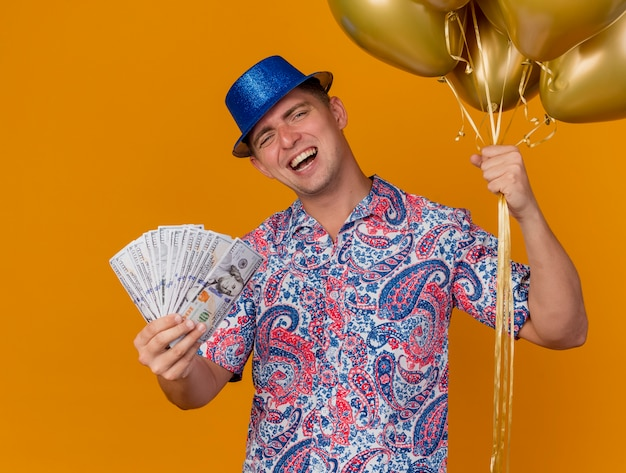 Joyful young party guy wearing blue hat holding balloons with cash isolated on orange