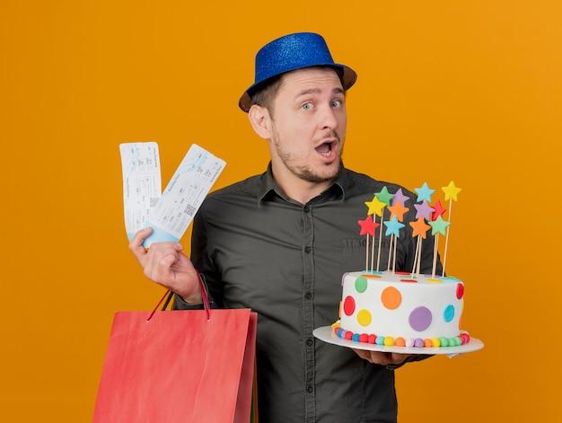 오렌지에 고립 된 선물 가방과 티켓으로 케이크를 들고 파란색 모자를 쓰고 즐거운 젊은 파티 남자