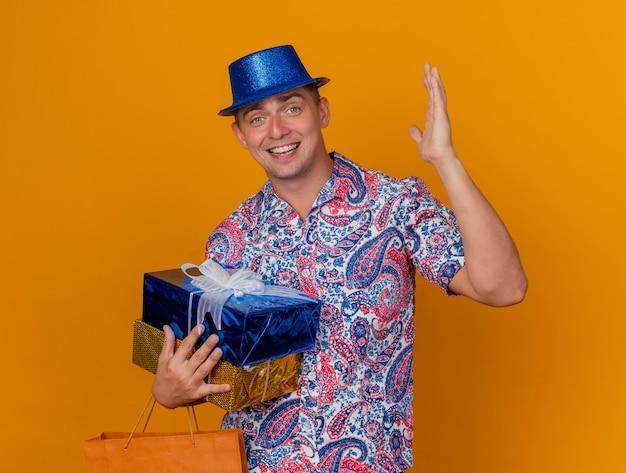 オレンジ色の背景で隔離手を上げるバッグとギフトボックスを保持している青い帽子をかぶってうれしそうな若いパーティー男