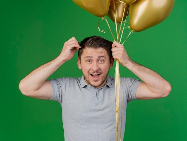Ragazzo allegro del partito giovane che indossa la camicia grigia che tiene palloncini e capelli afferrati isolati su verde