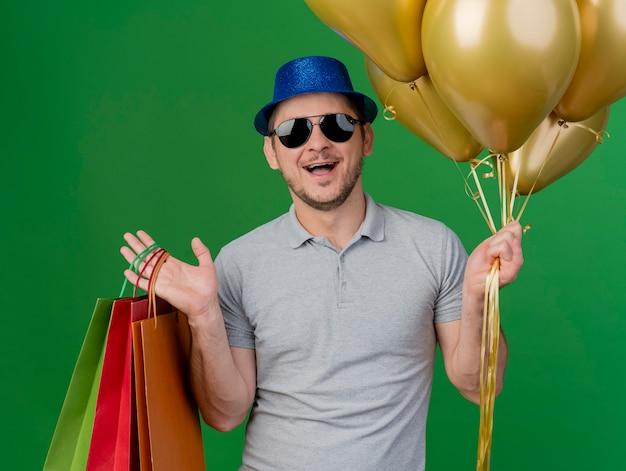 파티 모자와 녹색에 고립 된 풍선 선물 가방을 들고 안경을 쓰고 즐거운 젊은 파티 남자