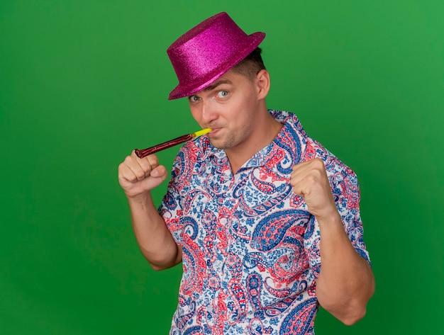Радостный молодой тусовщик в розовой шляпе, дует вентилятор, показывая жест да, изолированный на зеленом фоне