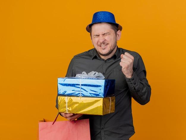 선물 상자와 오렌지에 고립 된 예 제스처를 보여주는 가방을 들고 파란색 모자를 쓰고 눈을 감고 즐거운 젊은 파티 녀석