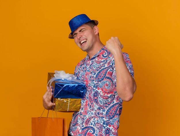 오렌지에 고립 예 제스처를 보여주는 가방 선물 상자를 들고 파란색 모자를 쓰고 눈을 감고 즐거운 젊은 파티 남자