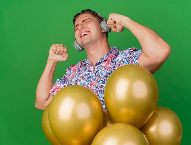 Ragazzo allegro festa giovane con gli occhi chiusi che indossa la camicia colorata e le cuffie in piedi dietro i palloncini che mostrano il gesto di sì isolato sul verde