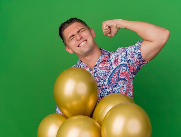 Ragazzo allegro giovane partito con gli occhi chiusi che indossa la camicia colorata in piedi dietro i palloncini che mostra il gesto di sì isolato sul verde