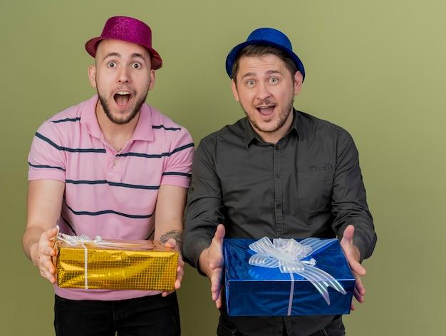 オリーブグリーンで隔離のギフトボックスを差し出す赤と青の帽子をかぶってうれしそうな若いパーティーの男