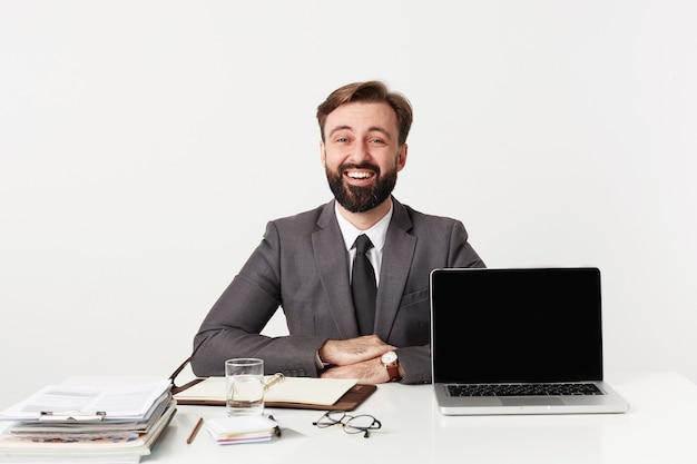 灰色のスーツとネクタイを着たうれしそうな若いかわいいひげを生やした男は、現代のラップトップとノートブックでオフィスで働いて、テーブルに手を組んで、正面を見ながら元気に笑っています