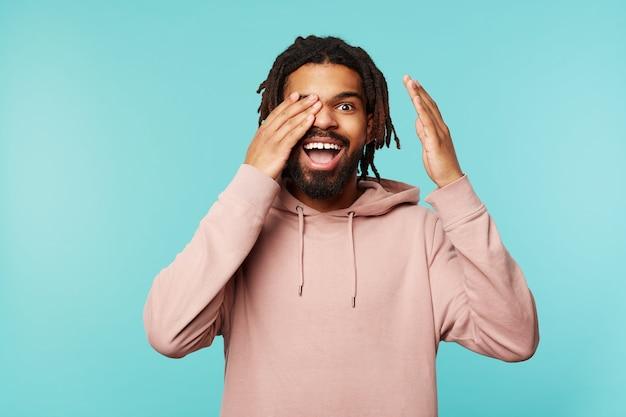 Gioioso giovane piuttosto barbuto con la pelle scura tenendo la mano alzata sul suo occhio e guardando allegramente la fotocamera con un ampio sorriso, isolato su sfondo blu