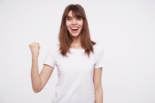 Joyful young pretty blue-eyed brunette female looking happily  with broad smile and raising her fist up while standing over white wall, being in high spirit