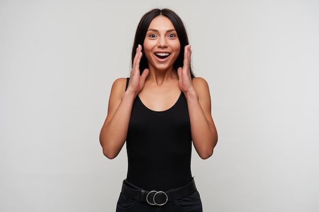 うれしそうな若いかなりブルネットの茶色の目の女性は、口を開けて驚いて見て、感情的に手を上げて、白で隔離されています
