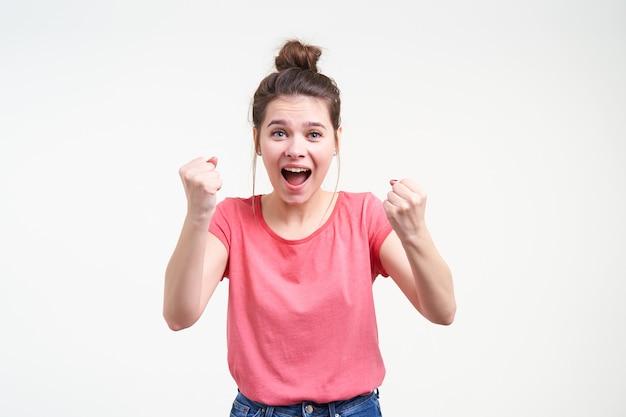 白い背景の上に立って、口を開けてカメラを興奮して見ながら幸せに拳を上げるお団子の髪型を持つうれしそうな若いかなりブルネットの女性