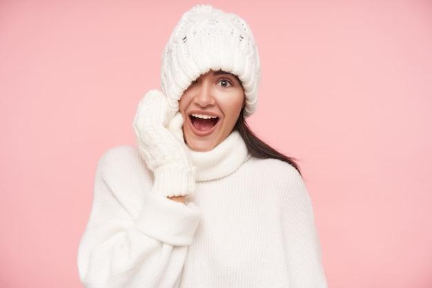 그녀의 머리에서 모자를 당기고 넓은 입으로 앞에 흥분을보고 자연 메이크업으로 즐거운 젊은 예쁜 갈색 머리 여자, 분홍색 벽 위에 절연