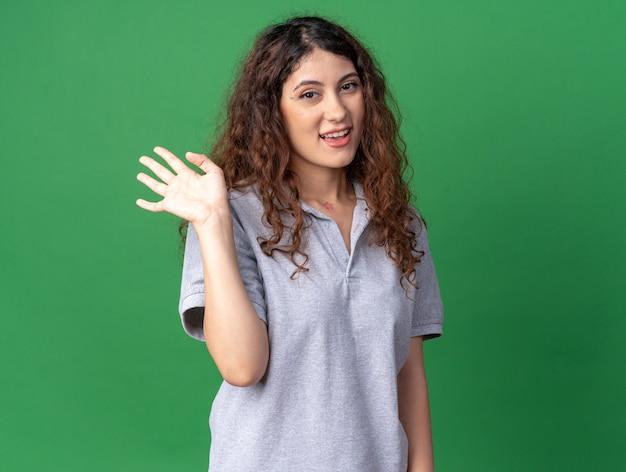 Joyful young pretty caucasian girl doing hi gesture
