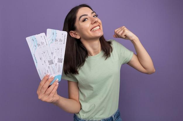 紫色の壁に隔離されたはいジェスチャーをしている飛行機のチケットを保持しているうれしそうな若いかなり白人の女の子