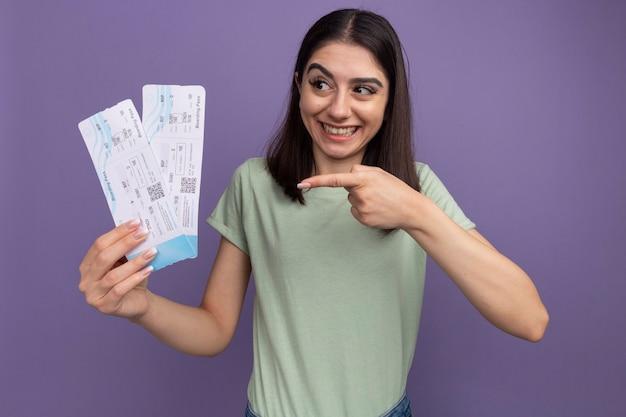 紫色の壁に隔離された側を見て飛行機のチケットを保持し、指しているうれしそうな若いかなり白人の女の子
