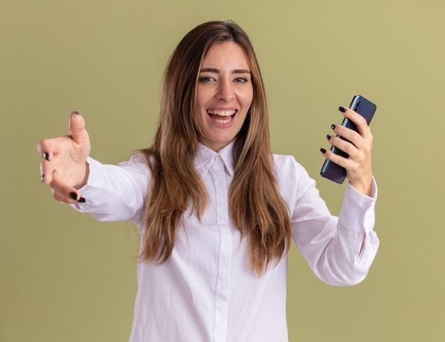 Радостная молодая симпатичная кавказская девушка держит телефон и протягивает руку, изолированную на оливково-зеленой стене с копией пространства