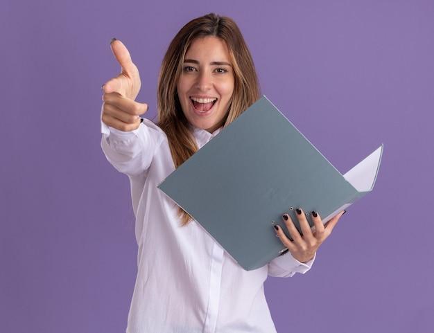 즐거운 젊은 백인 소녀는 파일 폴더와 복사 공간이 있는 보라색 벽에 격리된 카메라를 가리킵니다.