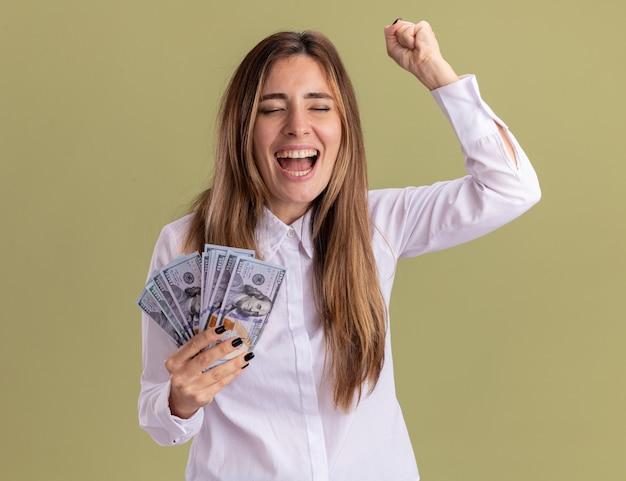 La giovane ragazza abbastanza caucasica allegra tiene i soldi e tiene il pugno su isolato sulla parete verde oliva con lo spazio della copia