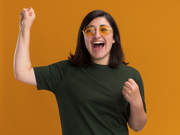 コピースペースとオレンジ色の壁に分離された上げられた握りこぶしで立っているサングラスのうれしそうな若いかなり白人の女の子