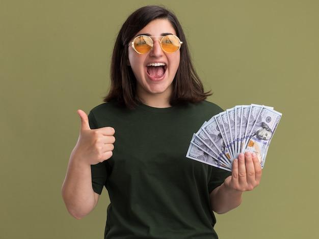 Радостная молодая симпатичная кавказская девушка в солнцезащитных очках показывает палец вверх и держит деньги