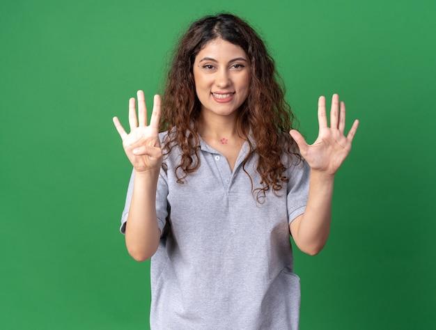복사 공간이 있는 녹색 벽에 격리된 손으로 9개를 보여주는 즐거운 젊은 백인 소녀
