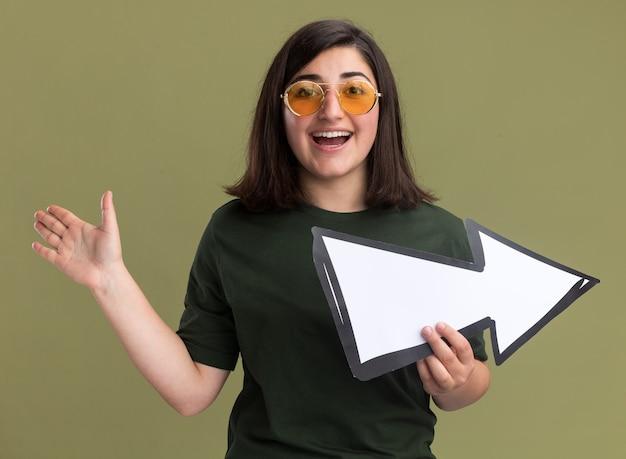 Gioiosa giovane ragazza abbastanza caucasica in occhiali da sole sta con la mano alzata e tiene il segno della freccia su verde oliva
