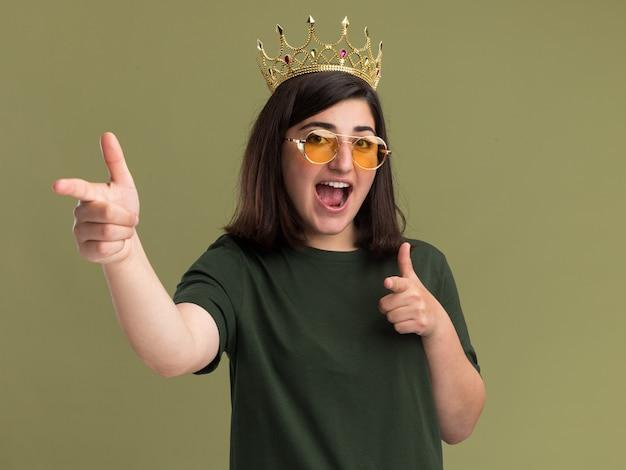 Gioiosa giovane bella ragazza caucasica in occhiali da sole con corona che punta a lato con due mani isolate sulla parete verde oliva con spazio per le copie