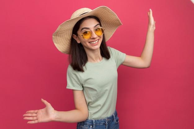 空の手を示すビーチ帽子とサングラスを身に着けているうれしそうな若いかなり白人の女の子
