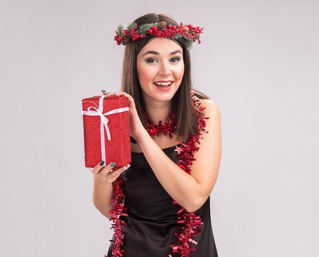 コピースペースと白い背景で隔離のカメラを見てギフトパッケージを保持している首の周りにクリスマスのヘッドリースと見掛け倒しの花輪を身に着けているうれしそうな若いかなり白人の女の子