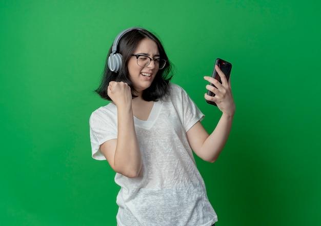 コピースペースで緑の背景に分離された目を閉じて拳を握り締める携帯電話を保持している眼鏡とヘッドフォンを身に着けているうれしそうな若いかなり白人の女の子