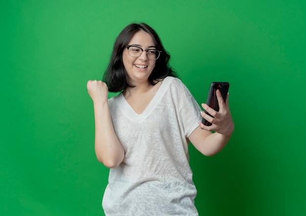 Радостная молодая симпатичная кавказская девушка в очках держит и смотрит на мобильный телефон и сжимает кулак