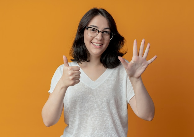 오렌지 배경에 고립 된 손으로 6을 보여주는 안경을 쓰고 즐거운 젊은 예쁜 백인 여자