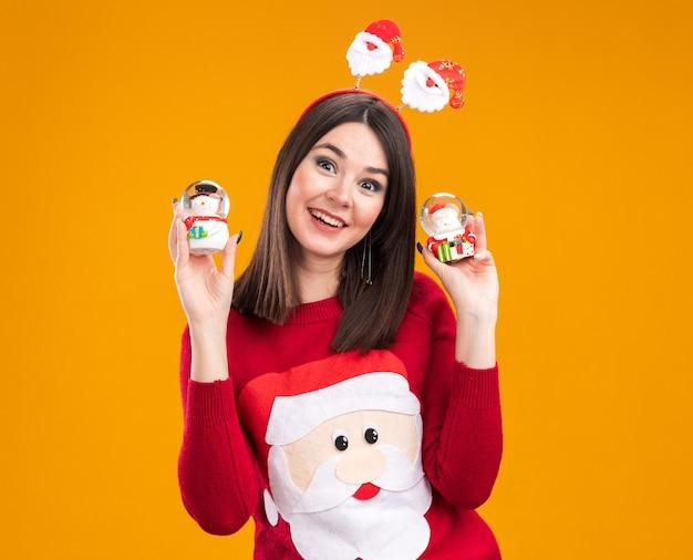 산타 클로스 머리띠와 눈사람과 산타 클로스 인형을 들고 스웨터를 입고 즐거운 젊은 예쁜 백인 여자 복사 공간 오렌지 배경에 고립 된 카메라를 찾고