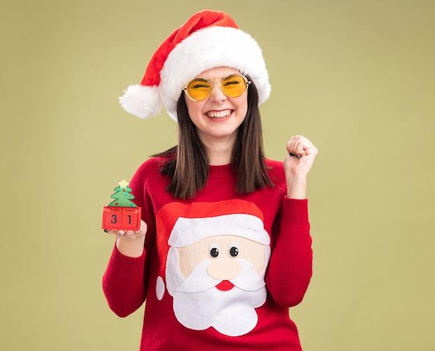 Радостная молодая симпатичная кавказская девушка в свитере санта-клауса и повязке на голову с очками, держащая елочную игрушку с датой, смотрящую в камеру, делает жест да, изолированный на оливково-зеленом фоне