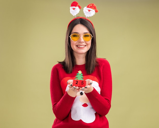 Радостная молодая симпатичная кавказская девушка в свитере санта-клауса и ободке с очками держит елочную игрушку с датой