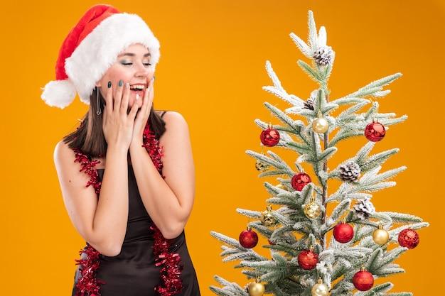 Gioiosa giovane bella ragazza caucasica che indossa il cappello della santa e la ghirlanda di orpelli intorno al collo in piedi vicino all'albero di natale decorato tenendo le mani sul viso guardando la risata laterale isolata su sfondo arancione