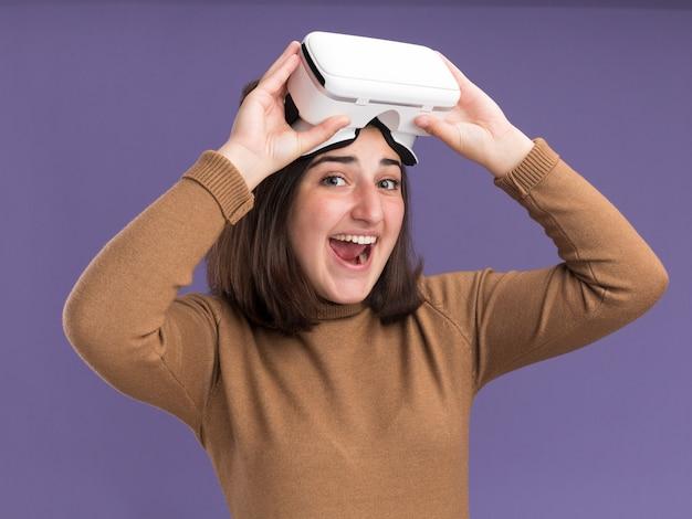 コピースペースで紫色の壁に分離されたvrヘッドセットを保持しているベレー帽の帽子を持つうれしそうな若いかなり白人の女の子