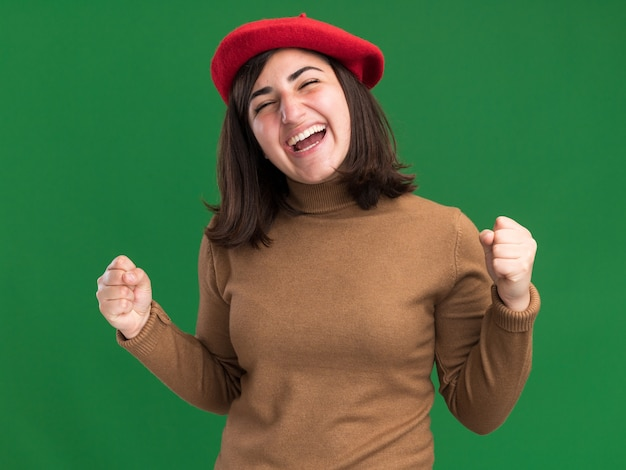 ベレー帽の帽子をかぶったうれしそうな若いかなり白人の女の子は、コピースペースで緑の壁に拳を隔離し続けます