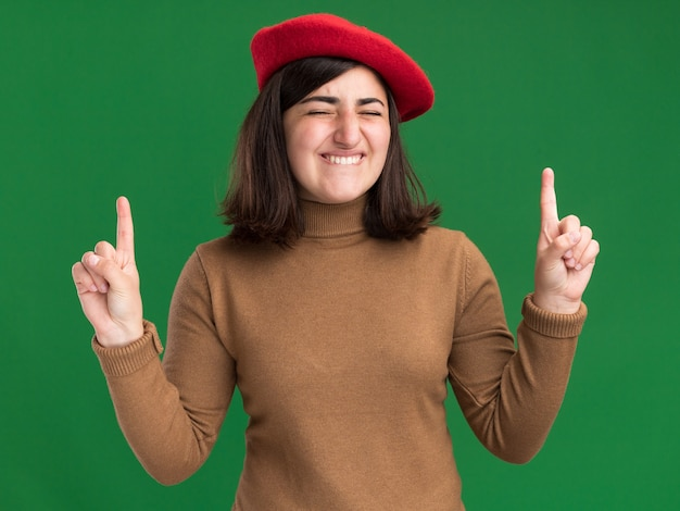 Joyful young pretty caucasian girl with beret hat stands with closed eyes pointing up isolated on green wall with copy space