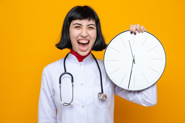 時計を保持している聴診器と医者の制服を着たうれしそうな若いかなり白人女性