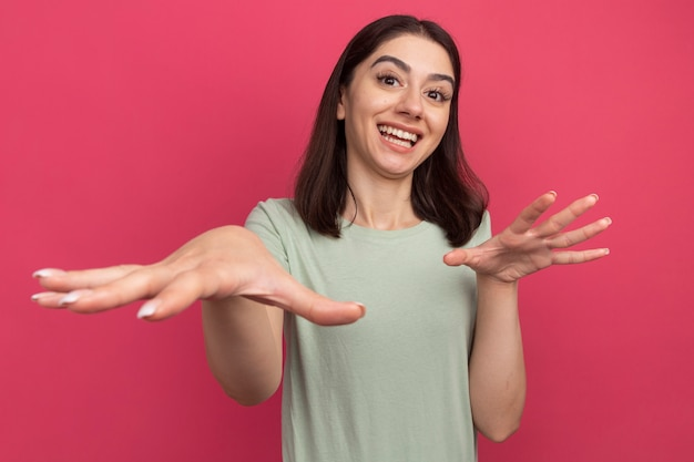 Joyful young pretty caucasian woman keeping hand in air