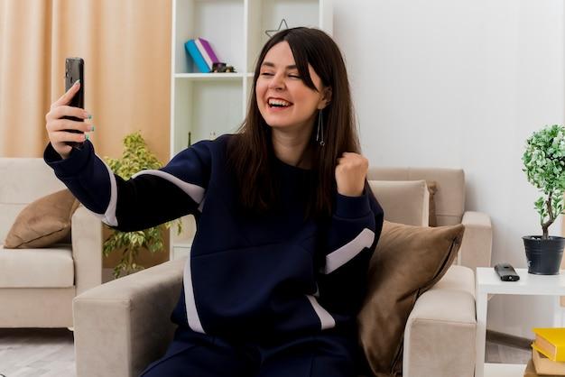 설계된 거실에서 안락의 자에 앉아 휴대 전화를 들고 예 제스처를하고 즐거운 젊은 예쁜 백인 여자