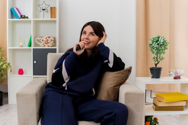 Радостная молодая симпатичная кавказская женщина, сидящая на кресле в дизайнерской гостиной, держит пульт дистанционного управления, держа руку на голове, глядя вверх, поет, используя пульт дистанционного управления в качестве микрофона