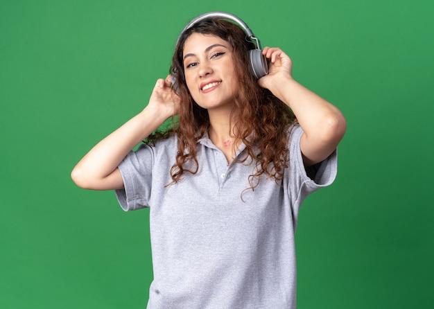 Gioiosa giovane bella donna caucasica che indossa e afferra le cuffie ascoltando musica
