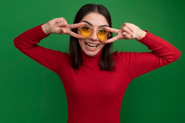 Joyful young pretty caucasian woman wearing sunglasses showing v-sign symbol near eyes