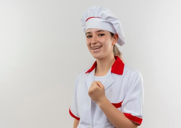Gioiosa giovane bella cuoca in uniforme da chef con bretelle dentali che stringe il pugno isolato sul muro bianco con spazio di copia