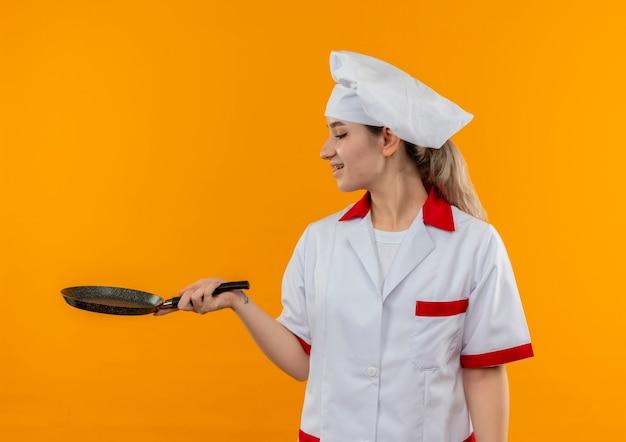 オレンジ色のスペースで隔離されたフライパンを保持し、見ている歯科用ブレースとシェフの制服を着たうれしそうな若いかわいい料理人