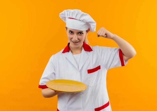 空の皿を保持し、オレンジ色のスペースで隔離の拳を上げる歯科用ブレースとシェフの制服を着たうれしそうな若いかわいい料理人