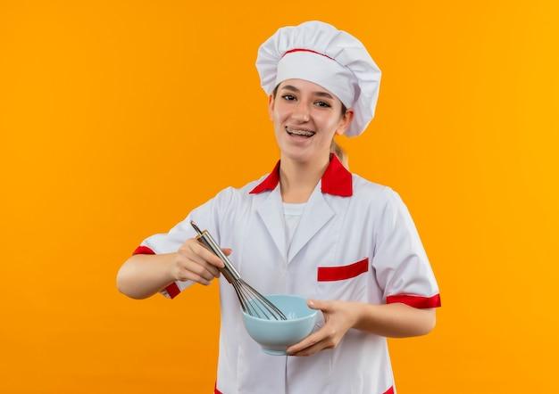 オレンジ色のスペースで隔離された泡立て器とボウルを保持している歯科用ブレースとシェフの制服を着たうれしそうな若いかわいい料理人